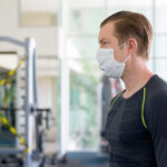 Portrait of young man at the gym with some exercise equipment use restricted for corona virus covid-19 safety measurements