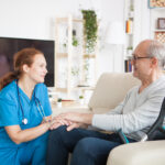 Female nurse smiling and talking with elderly age man in nursing home.
