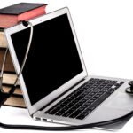 Old Books Pile With Silver Laptop and Stethoscope Isolated on White Background