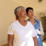 Side view of senior mixed race female patient and Asian female nurse standing in corridor at retirement home