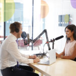 Young man interviewing a woman in a radio studio