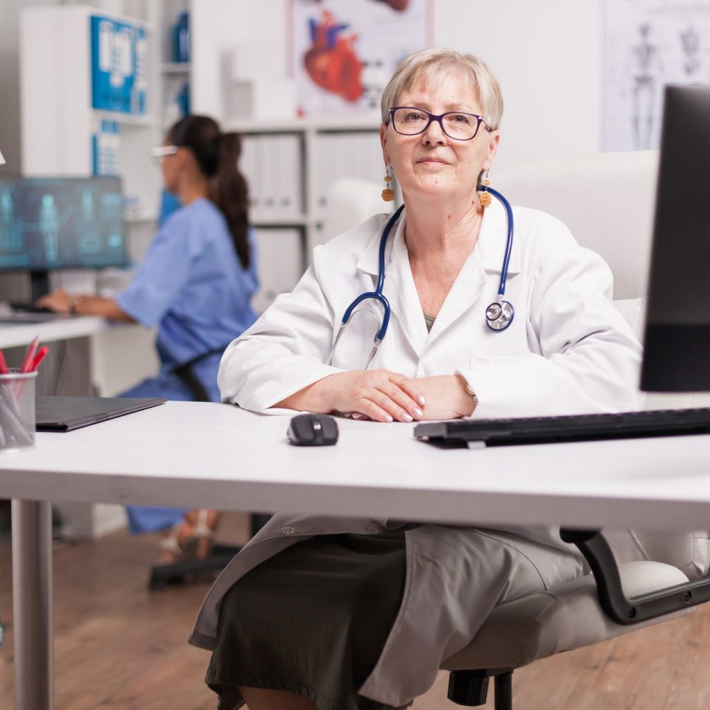 Mature medical therapist sitting at desk